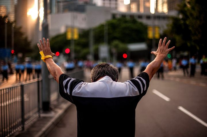 A man holds his hands in the air during protests in Hong Kong.