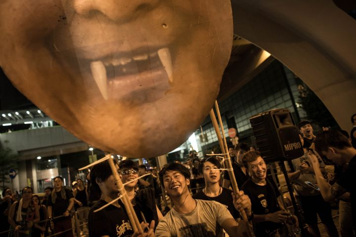Protesters carry a cardboard poster of C.Y.Leung, Hong Kong's Chief Executive, near the Hong Kong Government Complex.