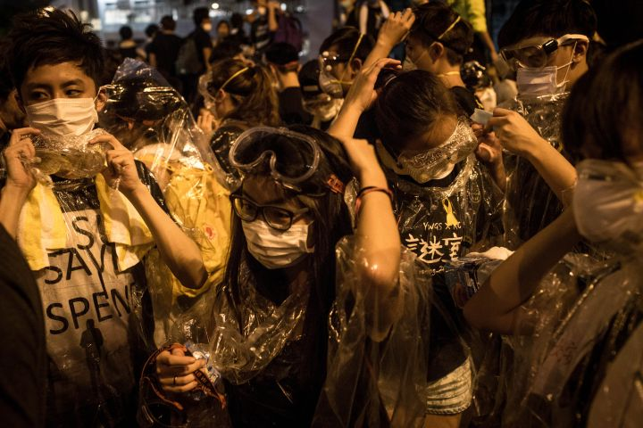 Demonstrators decked out in goggles, bandanas, t-shirts and plastic wrap gear up to face police lobbing tear gas at the crowd.