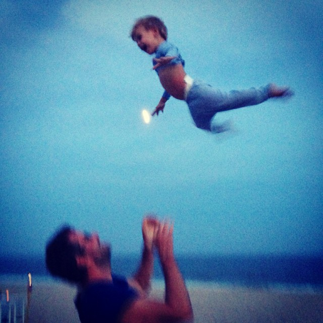 Daddy teaching son to fly while M snaps a pic.