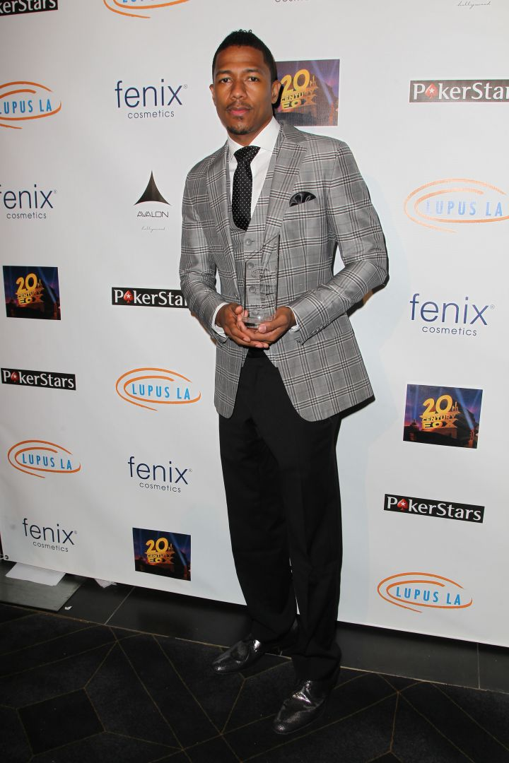 Nick Cannon hits the red carpet at the Stars Get Lucky For Lupus event in a fitted gray suit with black details.