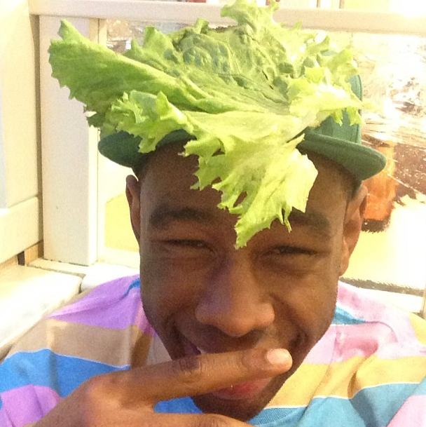 This is Tyler, The Creator with a piece of lettuce on his head.