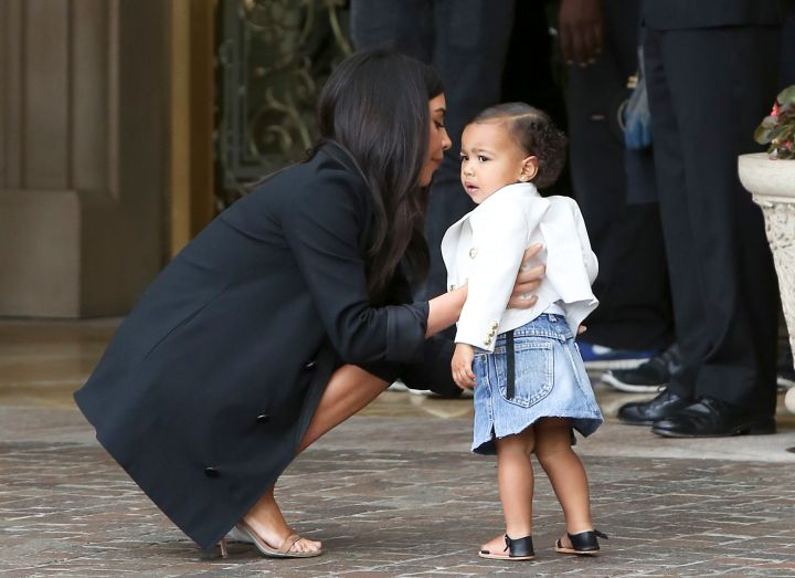 North does denim as she stays close to mom upon arrival.