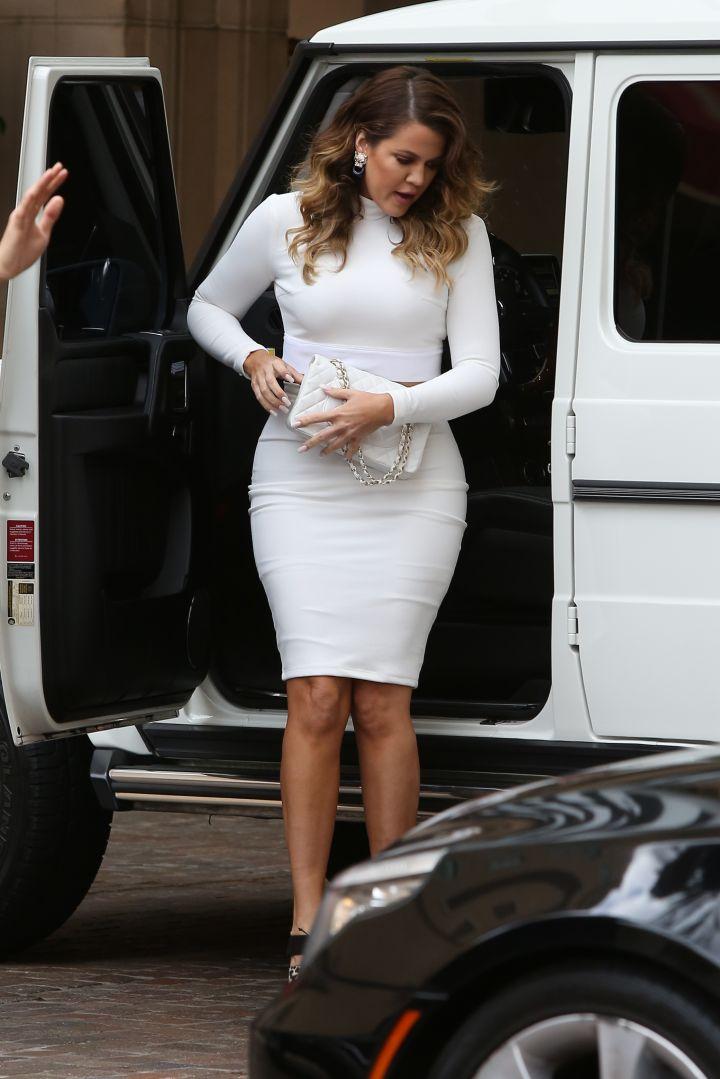 Khloe arrives in all white.