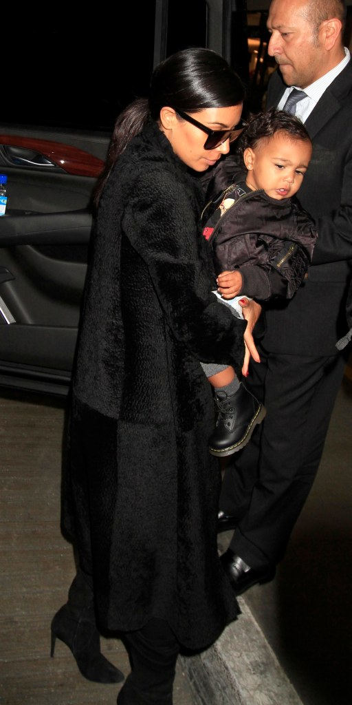 Kim Kardashian kisses baby North West as she carries her upon boarding a flight out of Los Angeles