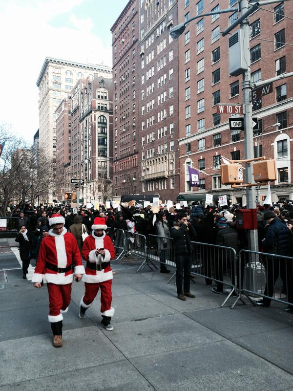 Santa Con participants face the interrupting protests happening through the streets.