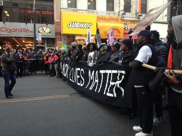 Protestors lead by holding up a 'Black Lives Matter' banner.