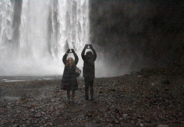 Mr. and Mrs. Carter throw up their roc in front of a beautiful waterfall.