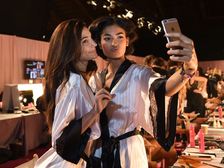 Izabel Goulart and Lais Ribeiro pose for a selfie backstage in hair and makeup at the Victoria's Secret Fashion Show 2014 in London.