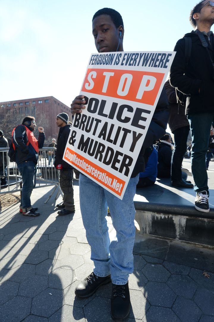 A protester holds up a sign to stop police brutality.