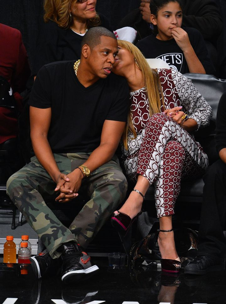 Bey tells her man a secret while sitting courtside.