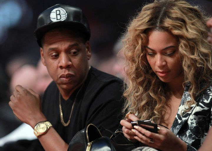Bey ain't the only one watching texts courtside. We caught you, Hov.