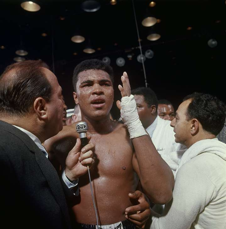 FEBRUARY 25, 1964: Cassius Clay (aka Muhammad Ali) talks into a reporter's mic after defeating Sonny Liston, not pictured in a World Heavyweight Title fight February 25, 1964 at Convention Hall in Miami, Florida.