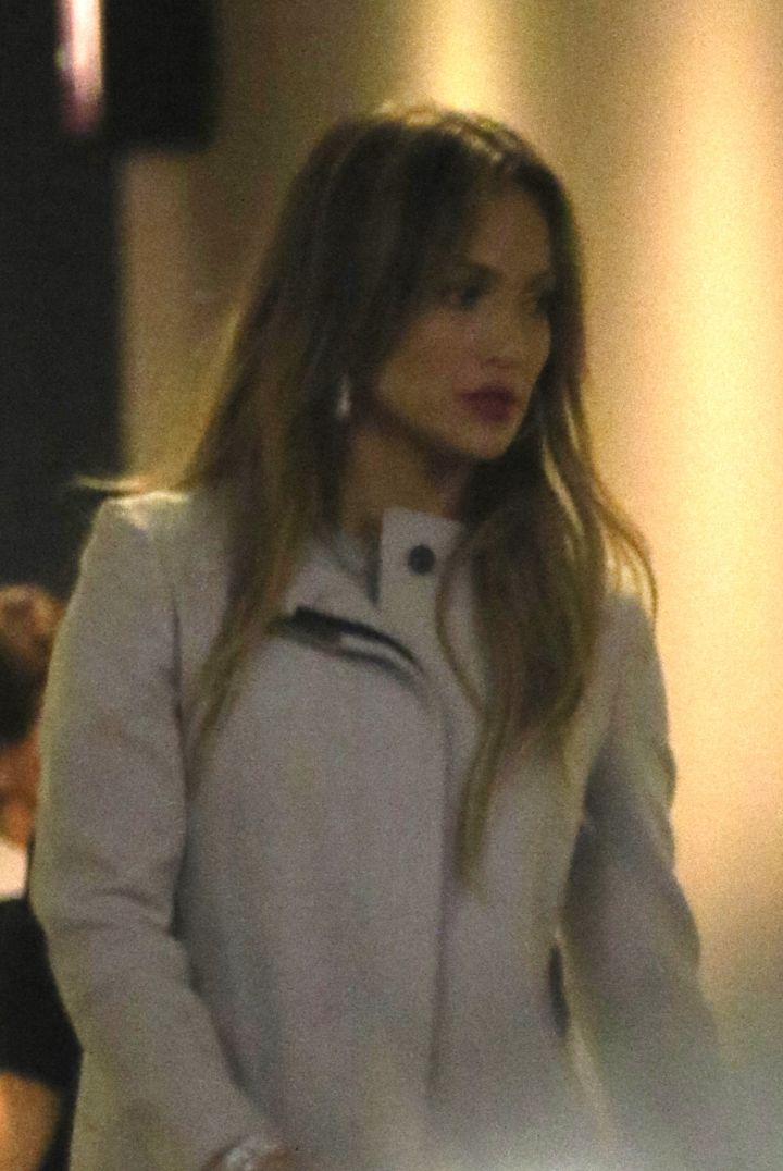 "Jennifer Lopez leaves the W Hotel in true ""Jenny from the block fashion,"" in a red lip and hoop earrings."