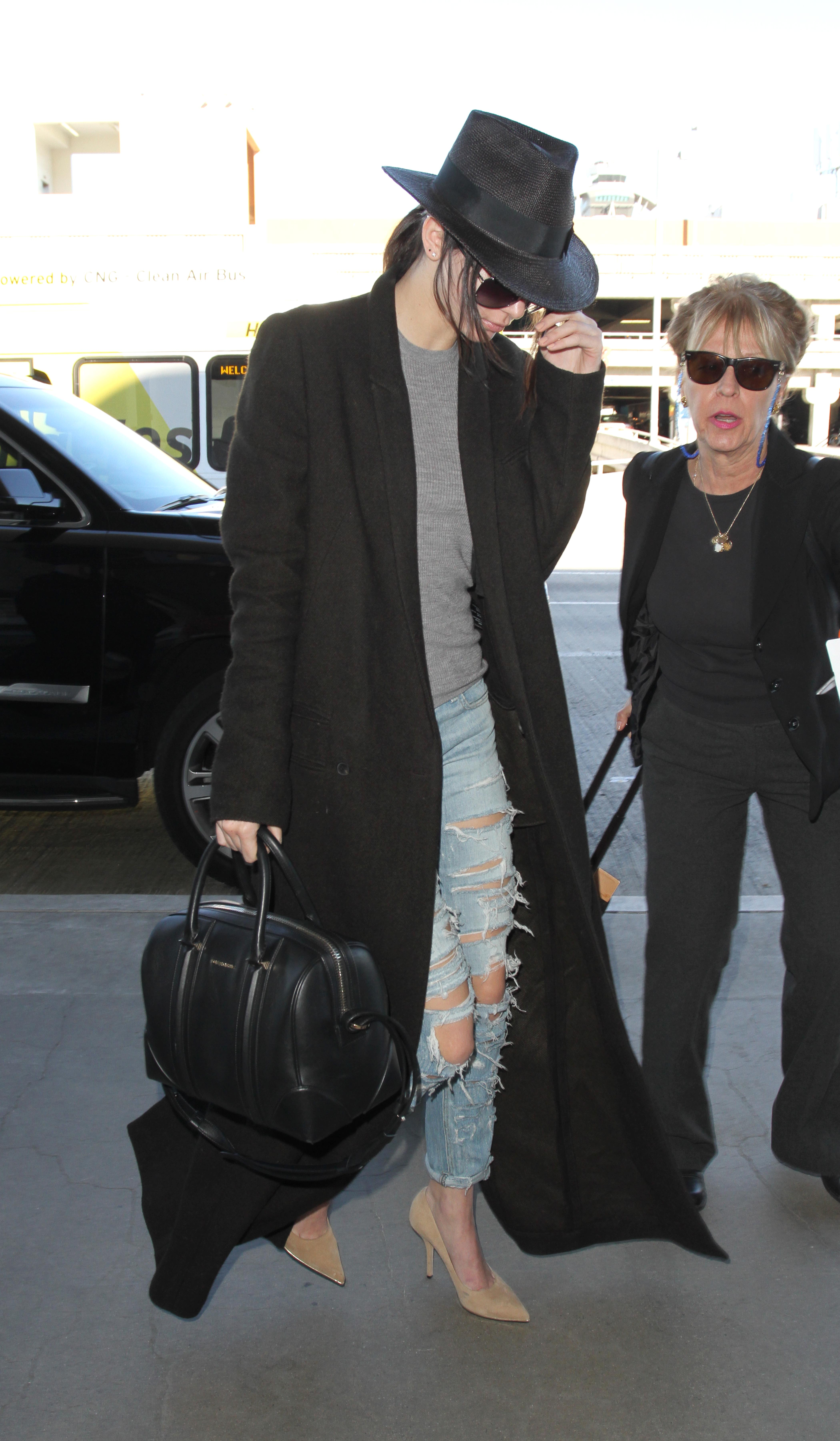 Kendall Jenner looks runway ready even as she sneaks through the airport signing autographs while wearing heels, torn jeans, an overcoat and a big floppy hat.
