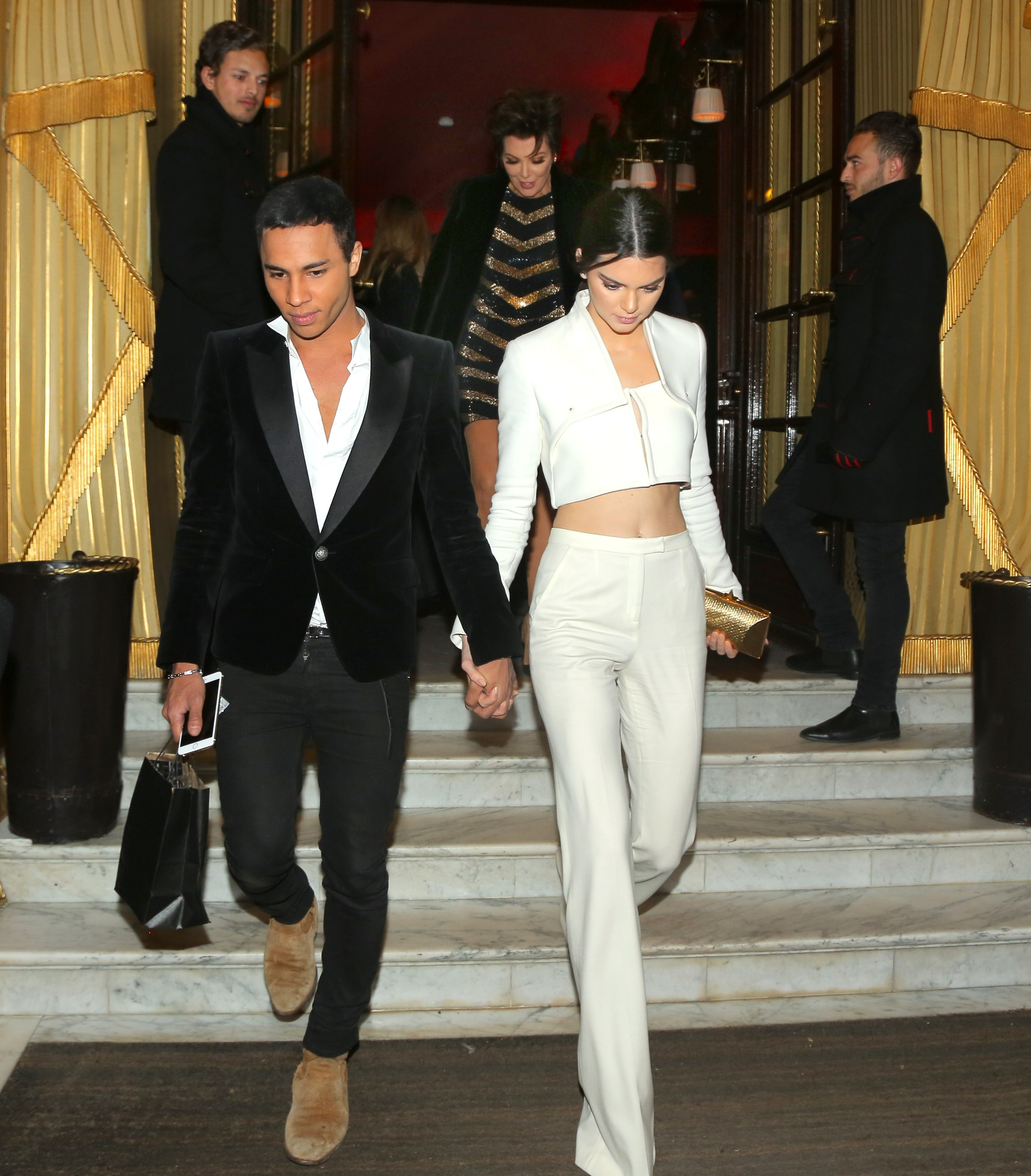 Kendall Jenner give a kiss on cheek and holds hands with desginer Oliver Rousteing of Balmain Paris as Kris Jenner smiles in delight