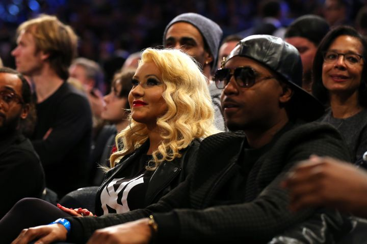 Christina Aguilera and Nas sit on the sidelines.
