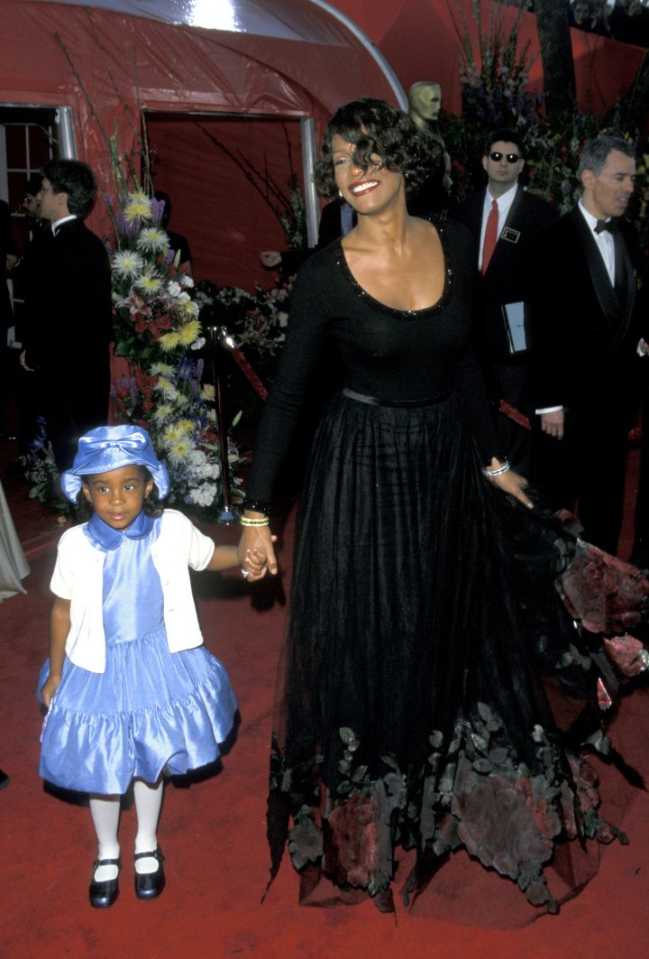 Daughter Bobbi walks the carpet with her mother Whitney Houston in March of 1999.