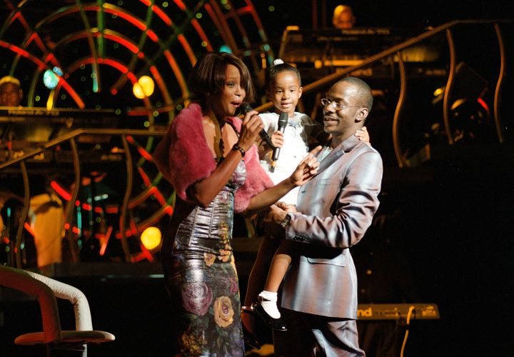 Whitney Houston with her daughter Bobbi Kristina Brown and husband Bobbi Brown onstage during a concert on July 16, 1999.