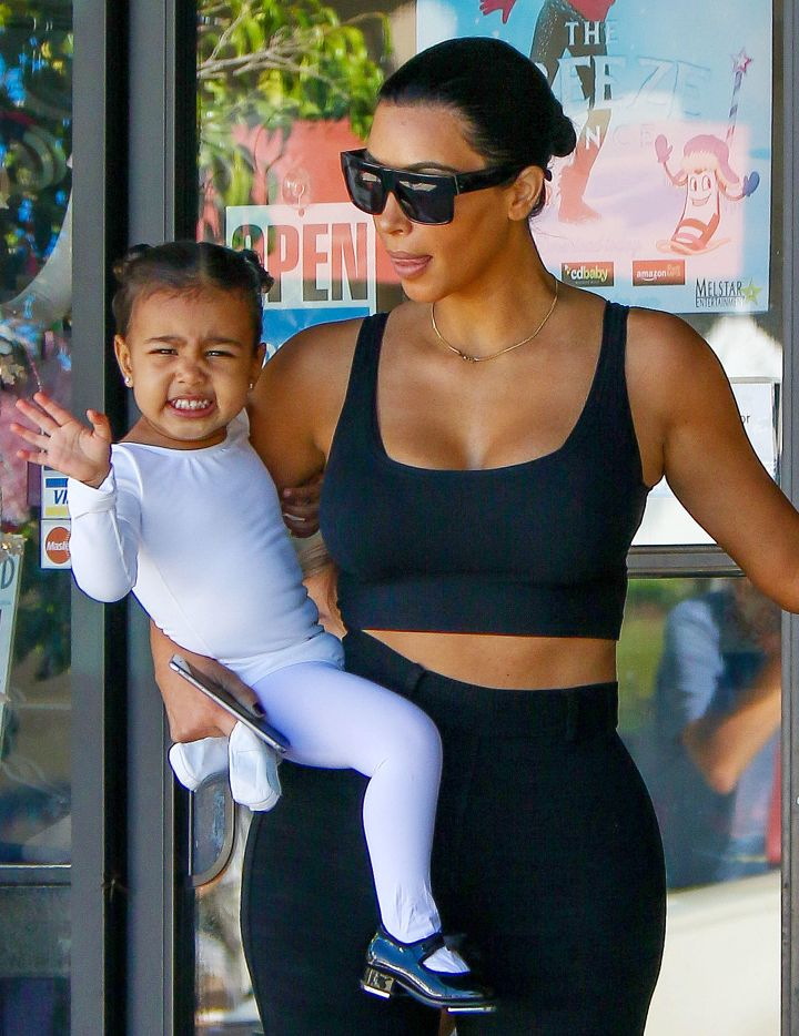 North shoos the paparazzi away from her mom.