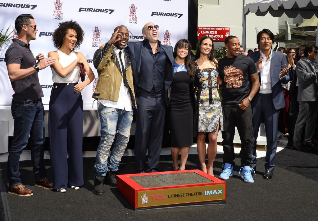 Vin Diesel poses with actors Tyrese Gibson (C-L) and Michelle Rodriguez (C-R) and other member of the 'Furious 7' cast as he is honored with a hand and footprint ceremony