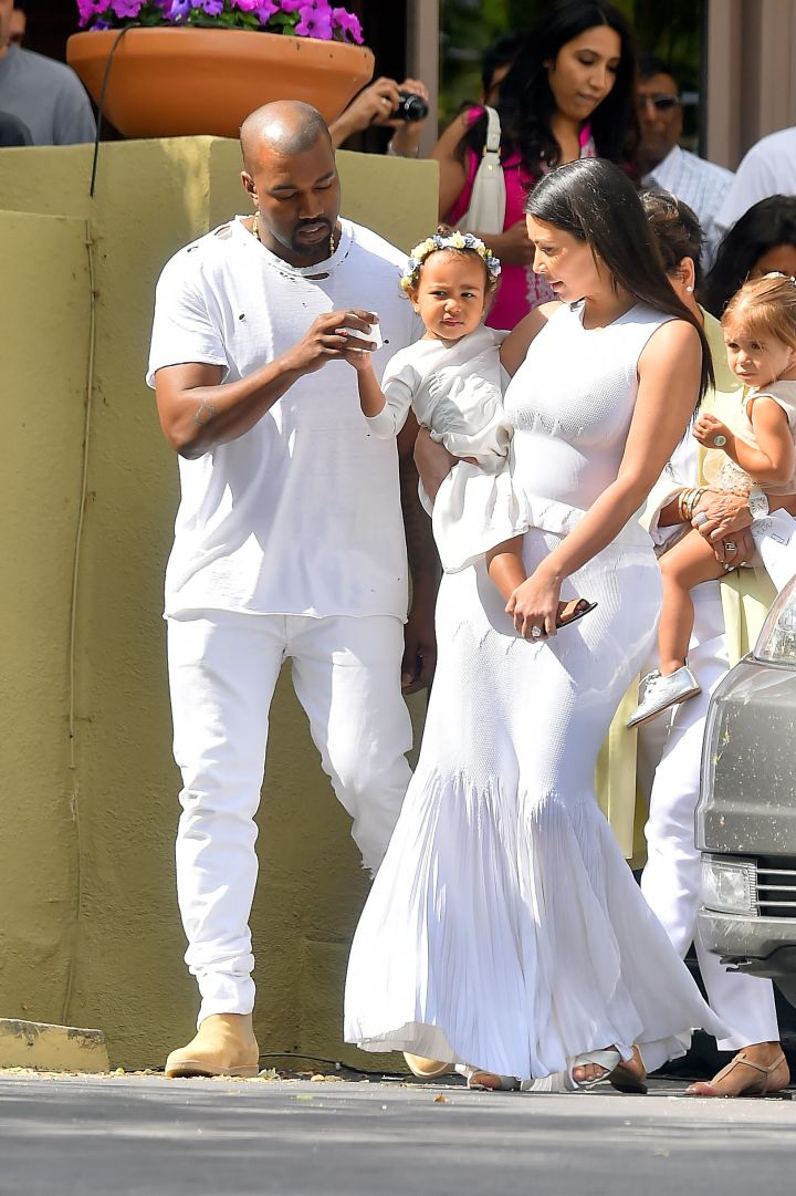 Meet the Wests. Kanye tends to his daughter North as Kim holds her before church.