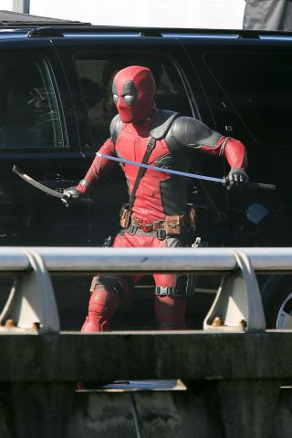 Ryan Reynolds, in costume as 'Deadpool' films a fight scene using two katana swords.