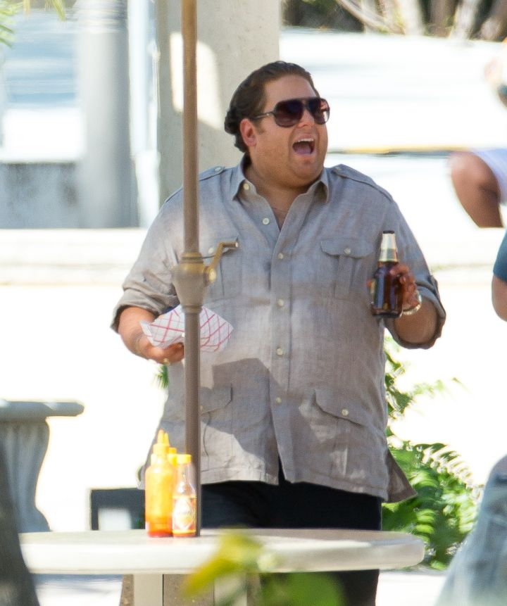 """Jonah Hill is making big moves as he sips on a beer and eats some food on set of his new film with Miles Teller called """"Arms and the Dudes."""""""