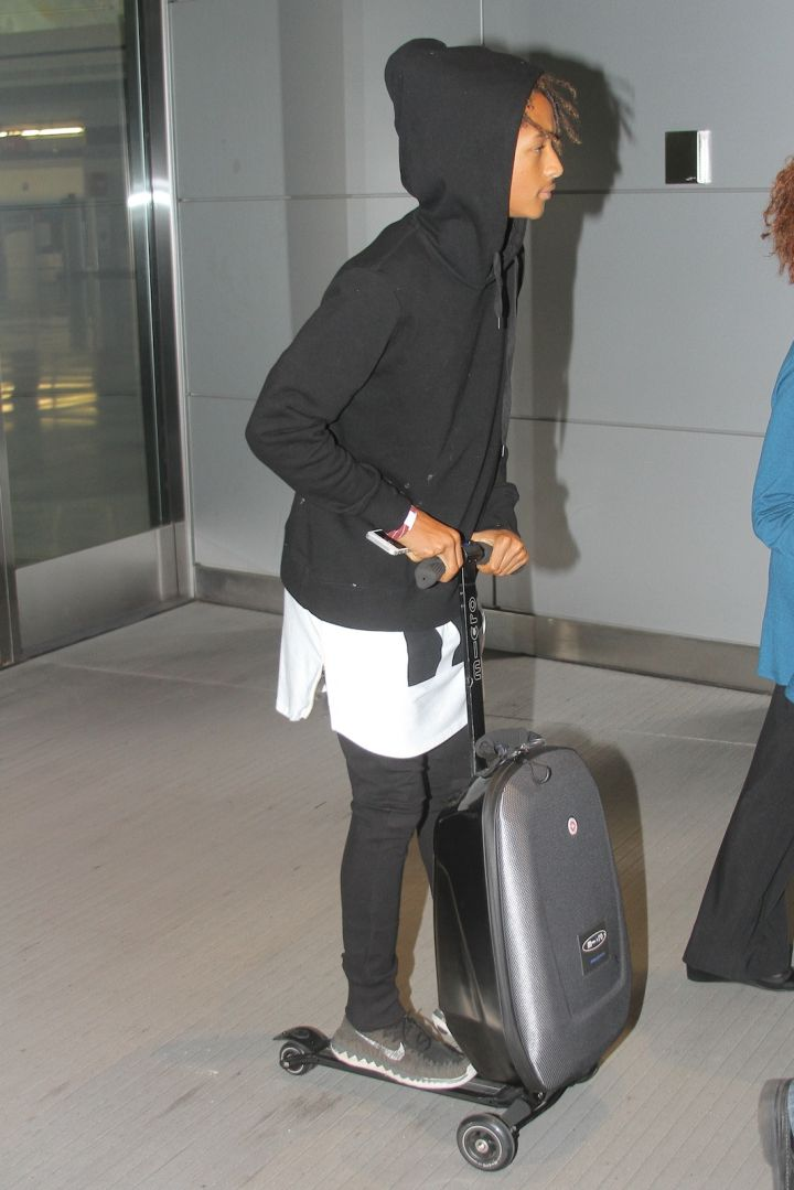 Jaden Smith riding a scooter suitcase.