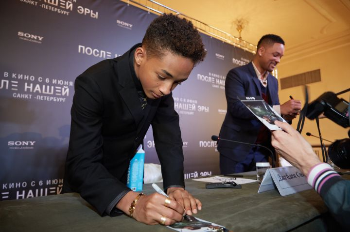 Jaden Smith signing his name on a picture of himself.