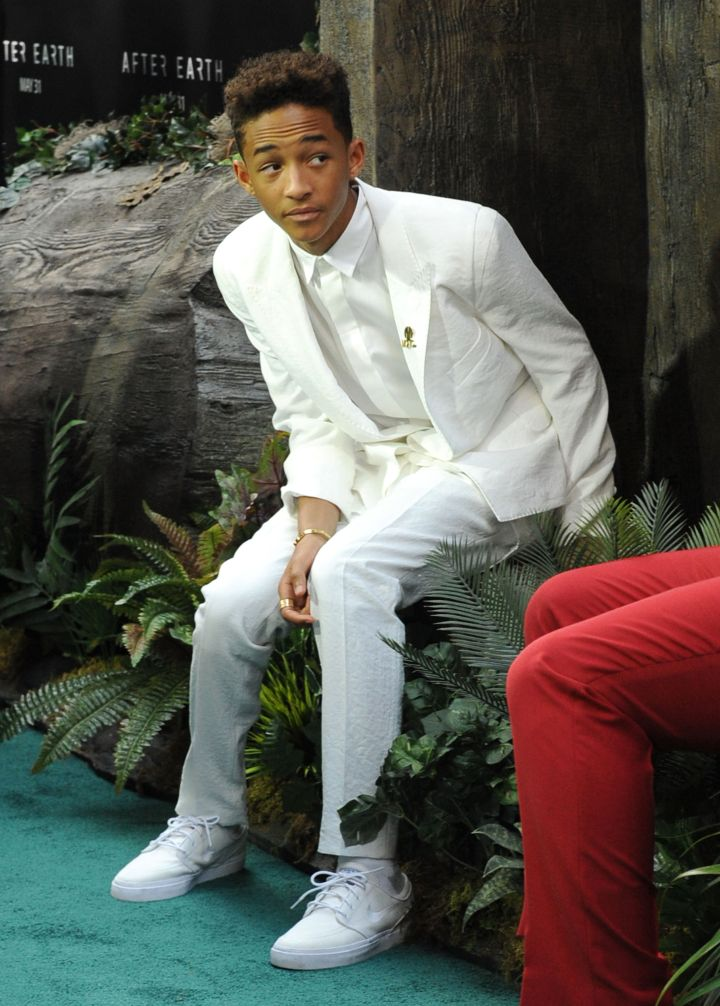 Jaden Smith sitting on a bush.