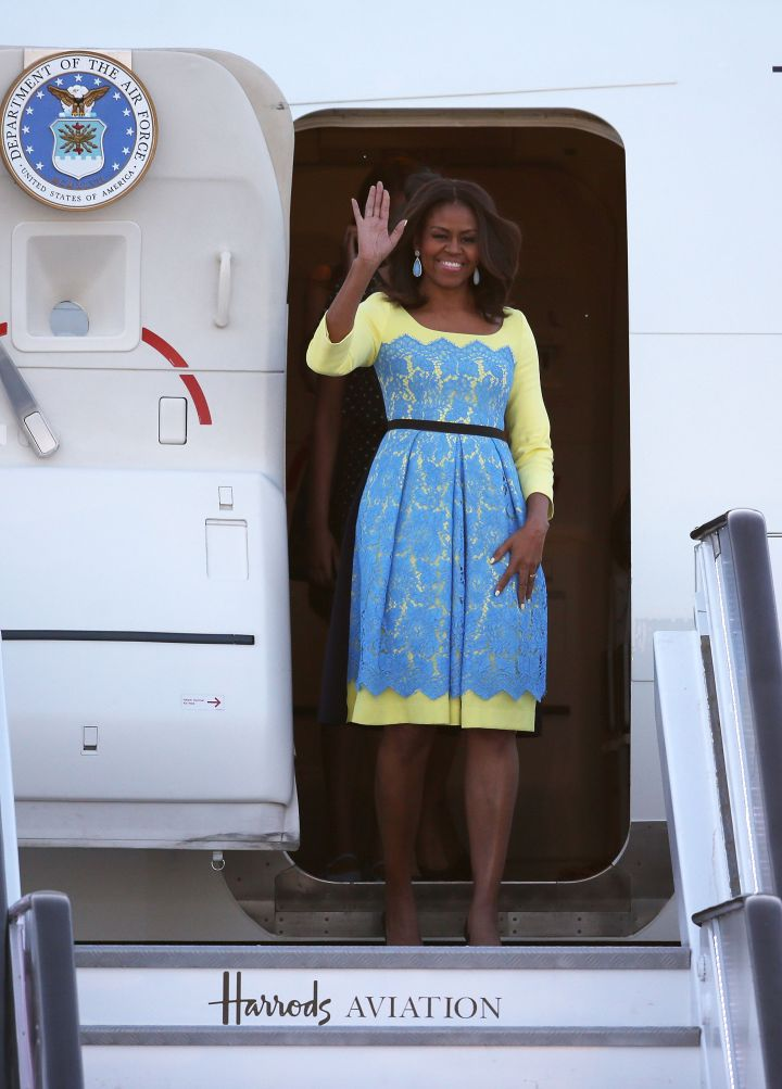Michelle Obama arrives in Europe wearing a blue and yellow frock.