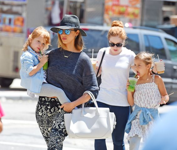 Jessica Alba carries daughter Haven in her arms as her other daughter Honor walks by