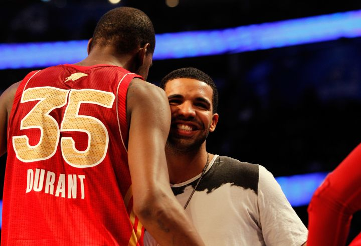 Drake cheeses while hugging Kevin Durant.