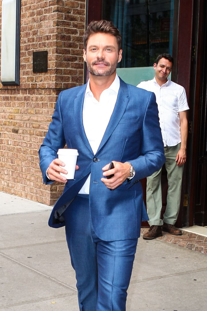 Ryan Seacrest rocks an electric blue suit as he leaves his hotel in NYC and takes photos with a fan.