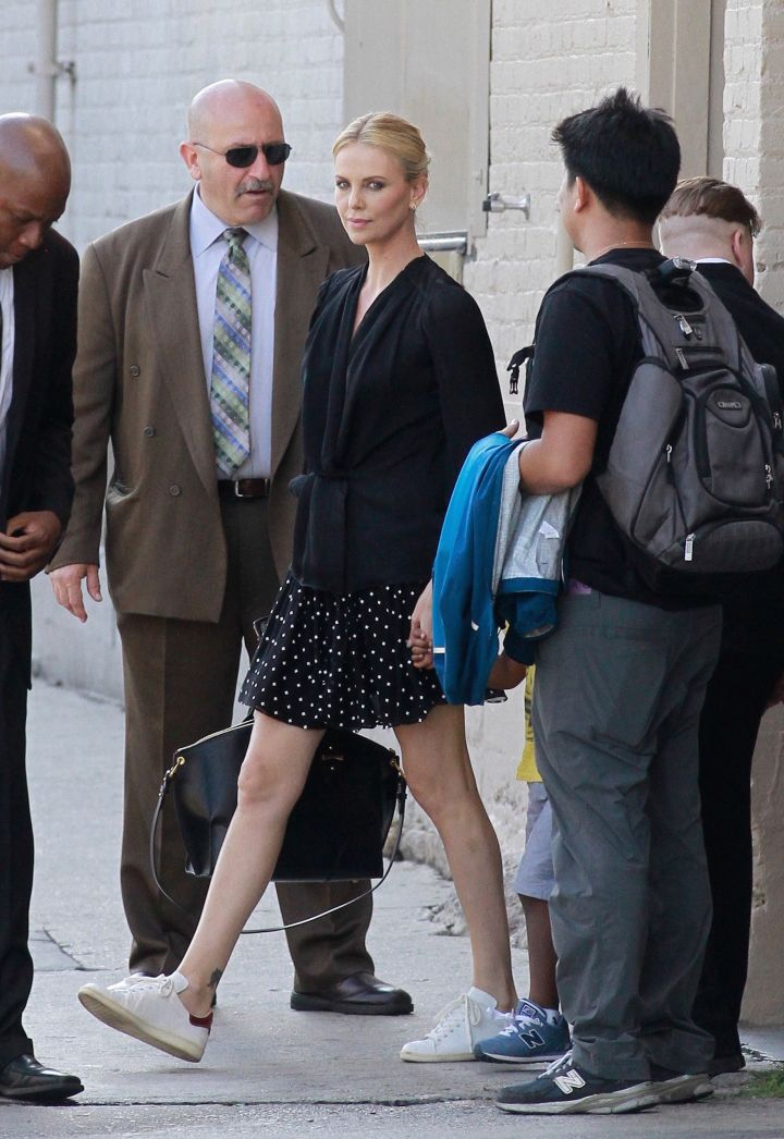 """Charlize Theron showed off her long legs in a short skirt outside of the """"Jimmy Kimmel Live"""" studios."""