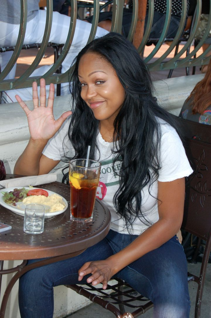 A baby-faced Meagan waves hello to the paparazzi while eating lunch.