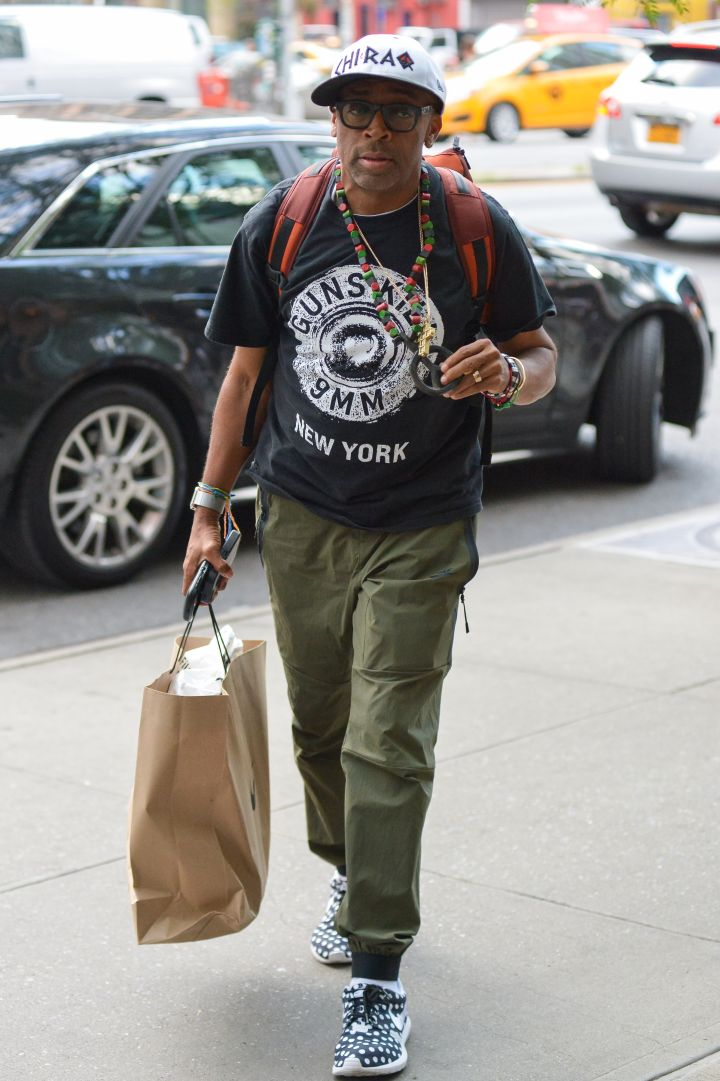 "Spike Lee is always willing to make a statement. Here he is holding up his peace sign necklace while wearing a ""Guns Kill"" t-shirt in downtown Manhattan."