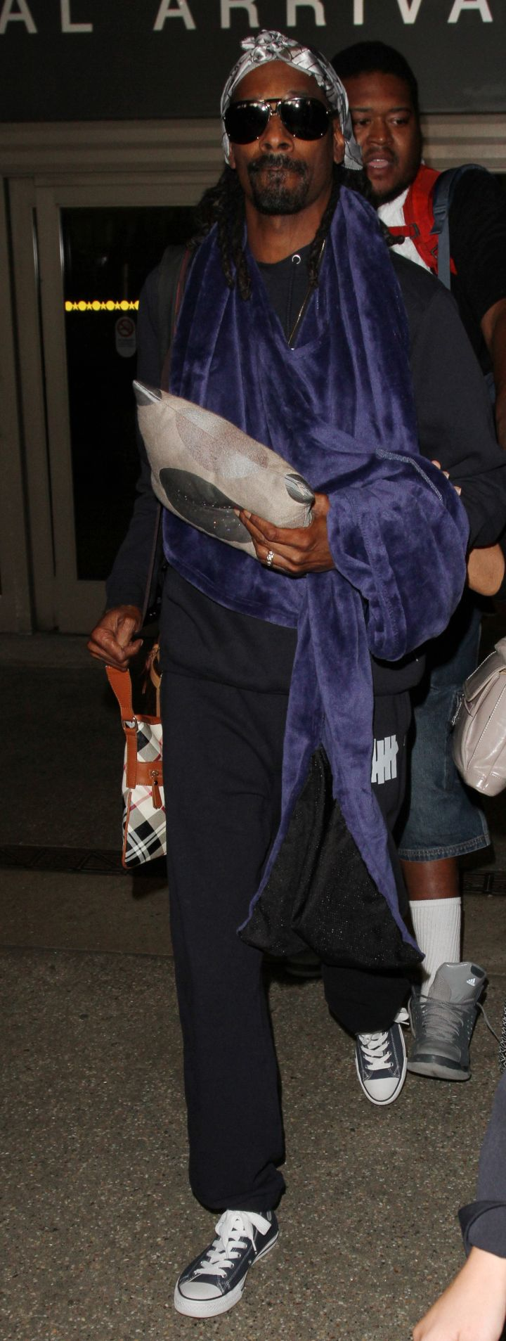 Hair tied, sweatpants, chilling with no makeup on. Snoop Dogg decided to keep it casual for his trip to LAX.