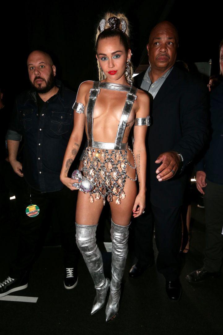 Miley Cyrus narrowly avoids nip-slips in Versace.