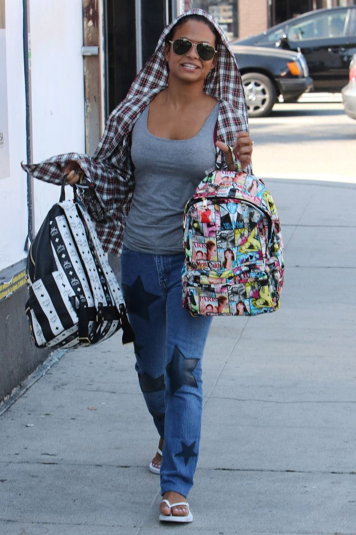 Christina Milian, you're going to hurt your back carrying all those bags like that.