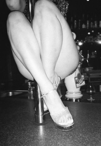 Woman pole dancing on bar counter