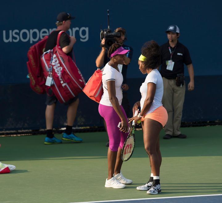 Serena Williams and Venus Williams stop for a brief chat on Day Three of the 2015 US Open.