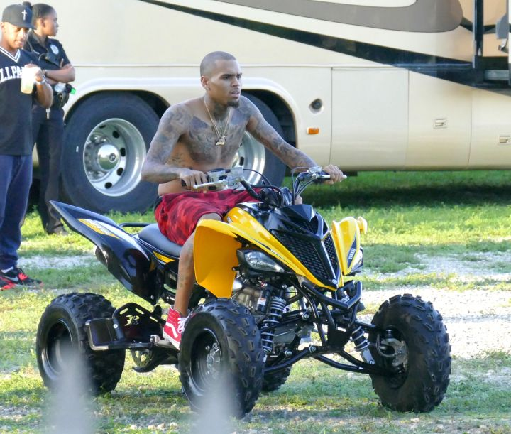 Vroom. Here's Chris Brown bicken back on an ATV Quad vehicle shirtless while on break from filming a music video with DJ Khaled, August Alsina, and Fetty Wap.
