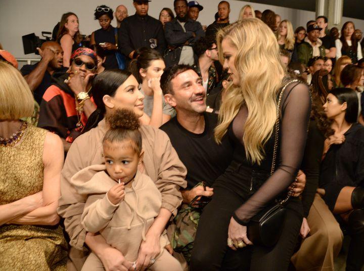 North West sucks on her lollipop while Kim talks to Khloe, sitting on Riccardo Tisci's lap.