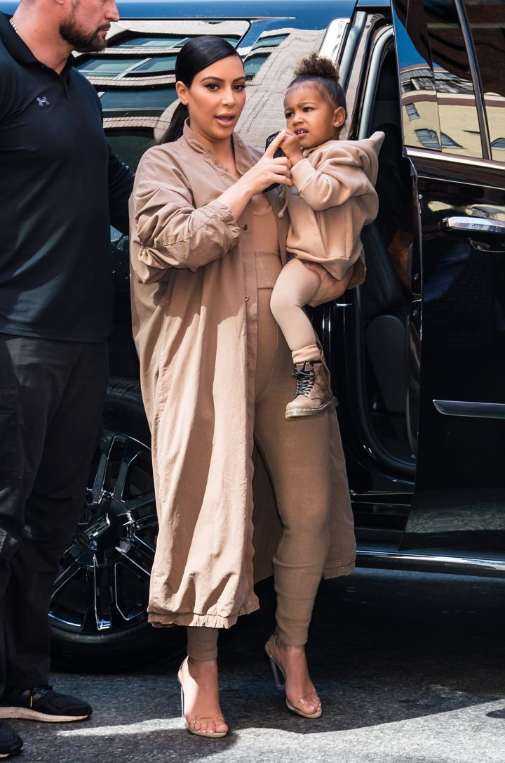 North West looks ready for action in her mommy, Kim Kardashian's arms.