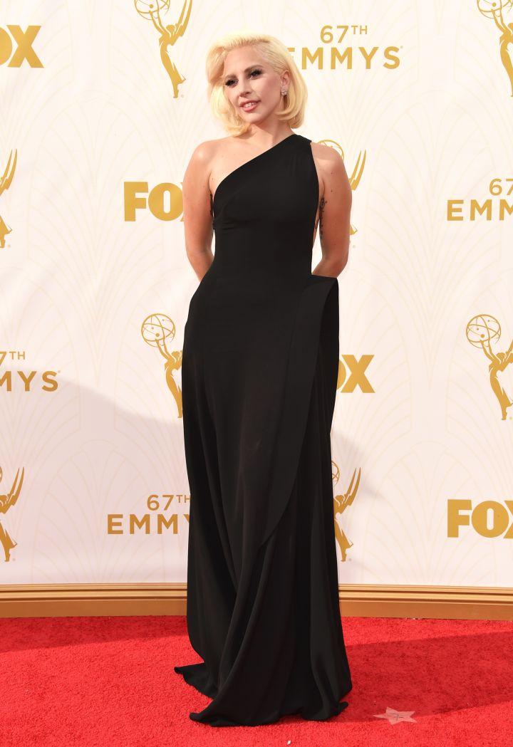Lady Gaga is wearing a one-shoulder black Brandon Maxwell gown