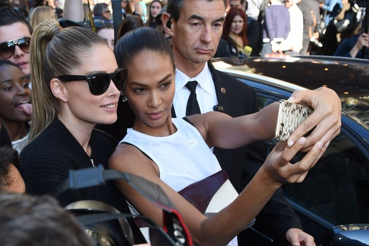 This dude is totally photobombing the selfie Doutzen Kroes and Joan Smalls are trying to take at the Balmain fashion show during Paris Fashion Week.