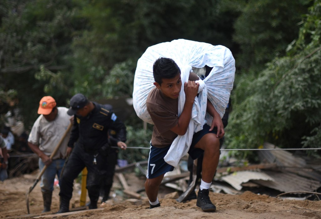 young man carries his belongings after a landslide late Thursday, following heavy rains, covered part of the village of El Cambray II, in Santa Catarina Pinula municipality