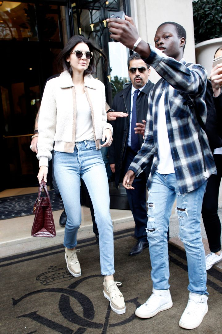 Kendall Jenner was leaving her hotel in Paris when an eager fan risked it all to get his selfie. Can't blame you bruh!